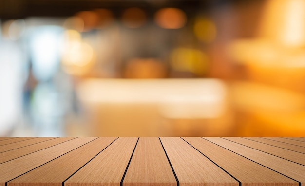 Modern brown wood tabletop with blurred restaurant bar cafe light color background