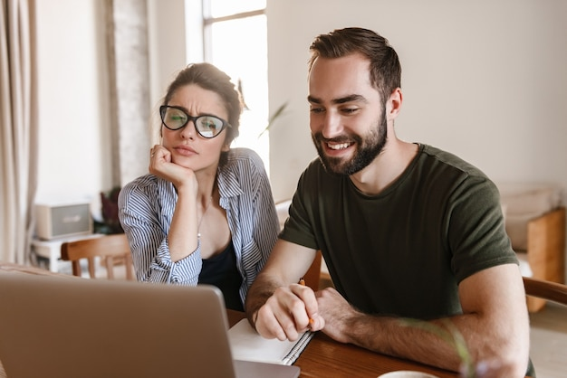 Modern brunette couple man and woman drinking coffee and working on laptop together while sitting at table at home