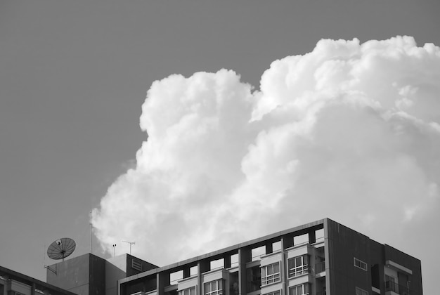 Modern building against fluffy cloudy sky in monochrome
