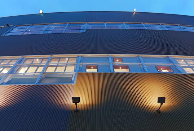 일본 도쿄, 노란색 조명과 푸른 하늘이 있는 황혼의 현대적인 건물 외관 추상 건축 배경