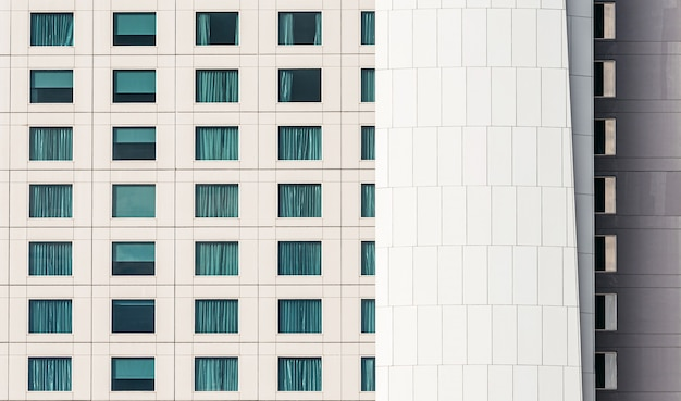 Modern building facade with window glass and white iron cladding building skin.