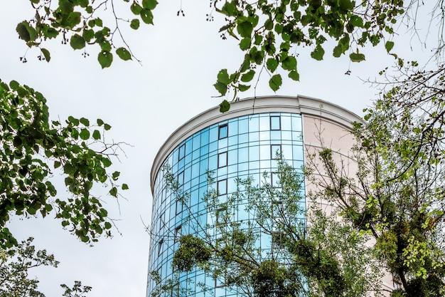 Современное здание круглой формы из бетона и стекла среди зеленых листьев деревьев