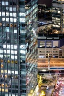 照明付きのモダンな建物の超高層ビルのガラス窓と道路上の交通