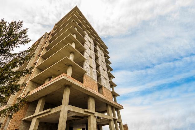 青い空を背景に建設中のモダンな建物。工事現場 Premium写真