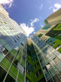 현대적인 건물입니다. 아래에서 위로 봅니다. 마천루는 구름에 도달합니다. 푸른 하늘에 대 한 녹색 유리 집입니다. 작가의 공간. 비문 또는 로고를 위한 큰 배경 공간