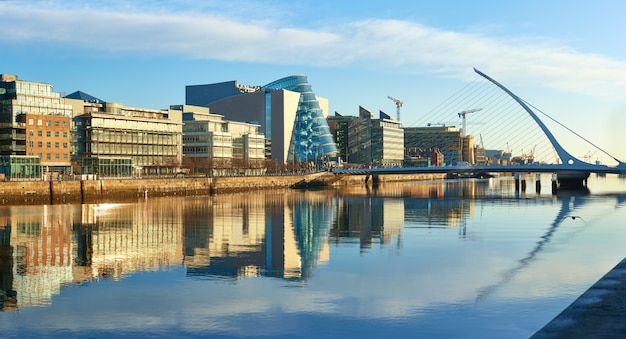 Modern buildings on liffey river in dublin and harp bridge