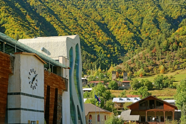 Modern buildings in mestia town center against early fall foliage on the nearby mountains georgia