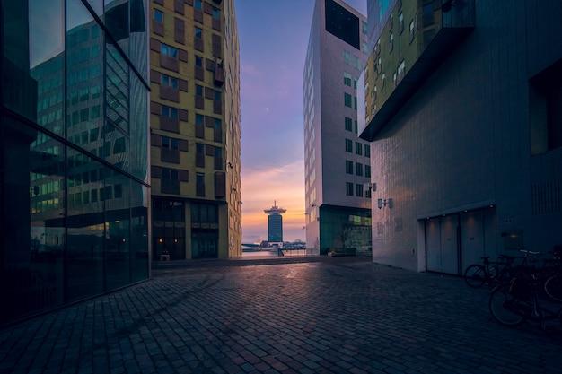 저녁에 일몰 동안 흐린 하늘 아래 유리창이있는 현대적인 건물