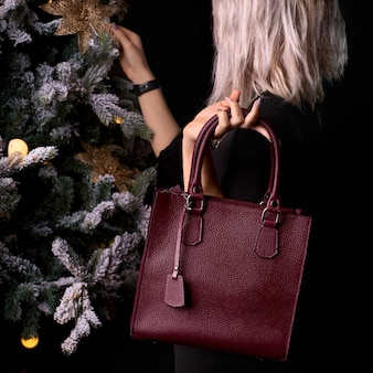 Современная бордовая кожаная сумка в женской руке. девушка возле елки