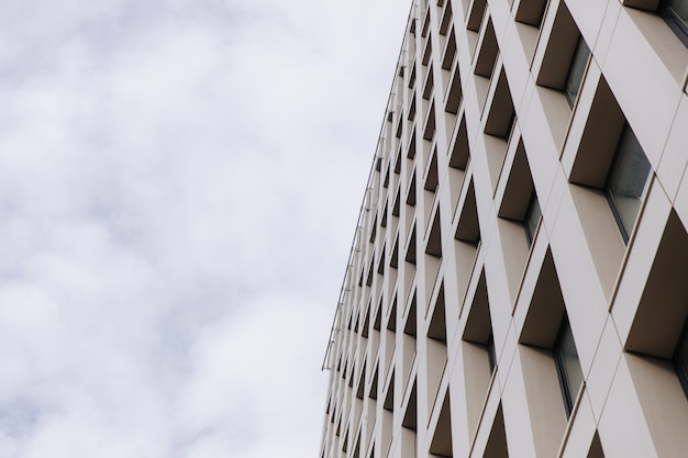 雲と青い空の上に構築する現代のビジネス。ハイオフィスセンターのローアングルビュー。デザインとエクステリアのコンセプト。