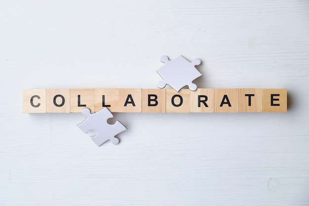 Modern business buzzword - collaborate. top view woodenpuzzle, blocks. top view.
