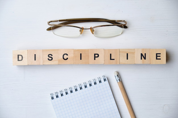 Modern business buzzword - discipline. top view on wooden table with blocks. top view.