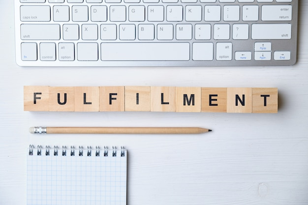 Modern business buzzword - fulfilment. top view on wooden table with blocks. top view.