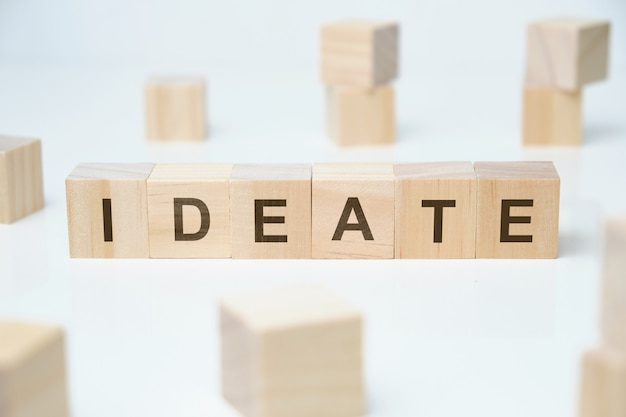 Modern business buzzword - ideate. word on wooden blocks on a white space.