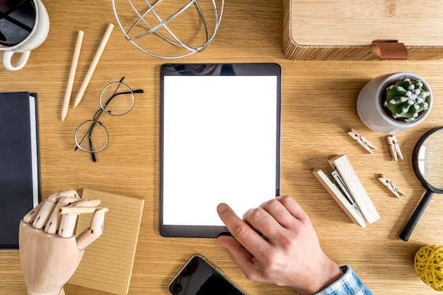Modern business composition on the home office with freelancer, mock up tablet screen, plant, notes, mobile phone and office supplies in stylish concept of home decor.
