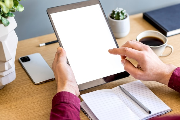 Modern business composition on the home office with freelancer,  tablet screen, plant, notes, mobile phone and office supplies in stylish concept of home decor.