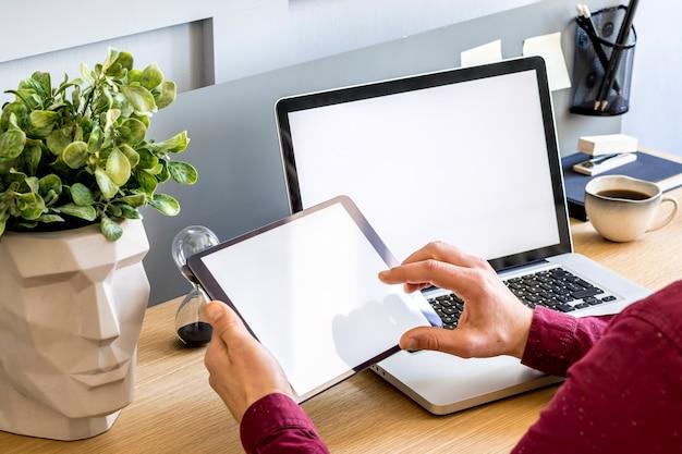 フリーランサー、モックアップタブレット画面、植物、メモ、携帯電話、および家の装飾のスタイリッシュなコンセプトの事務用品を備えたホームオフィスの現代的なビジネス構成。