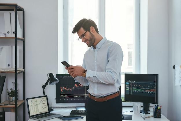 Современный деловой счастливый и успешный трейдер в официальной одежде смотрит на торговые графики и