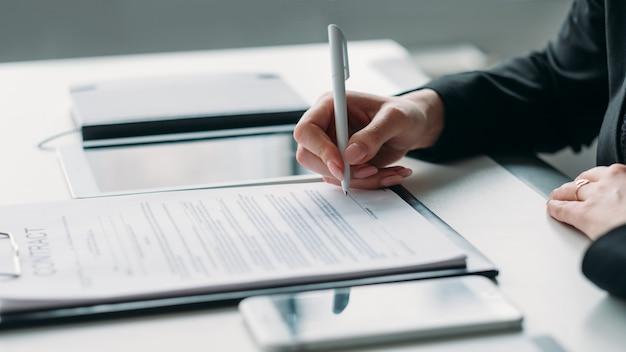 現代の事業投資。企業関係。契約に署名する女性の手のクローズアップ。
