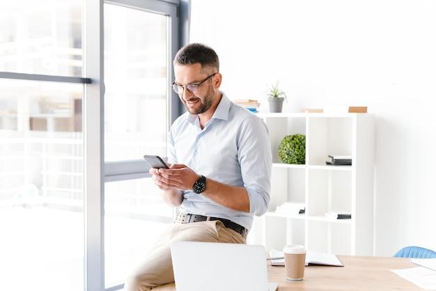 大きな窓の近くのオフィスのテーブルの上に座って、仕事にスマートフォンを使用して正式な摩耗で現代のビジネスの男性