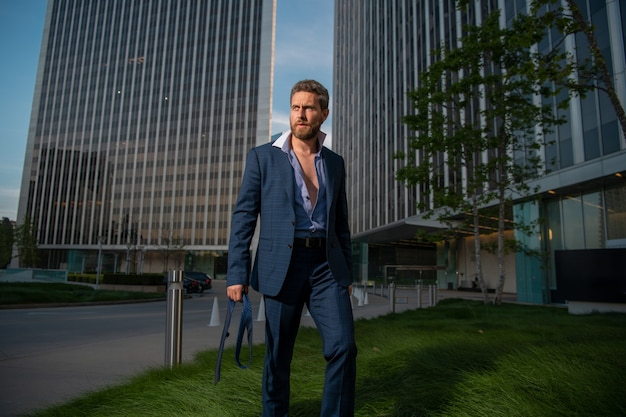Modern business man in suit standing outdoors with cityscape in the background
