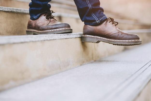 Современный деловой человек, работающий крупным планом ноги, спускается по лестнице в современном городе. в час пик на работу в офис спешат. в первое утро работы. лестница
