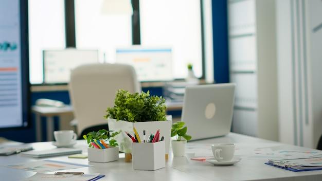 会議用テーブルと白い椅子を備えたモダンなビジネスミーティングゾーンのインテリア。誰もいないビジネスセンターのブレインストーミングエリア、モダンな家具、白い棚、青い壁のある空の部屋のショット