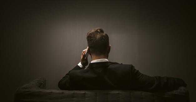 어두운 배경에서 현대 비즈니스 사람입니다. 휴대 전화 무선 통신 개념입니다. 이동 통신