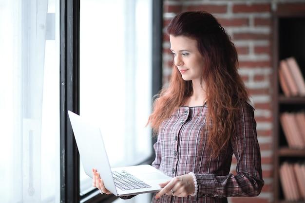 現代のビジネス女性はオフィスに立っているラップトップを使用しています