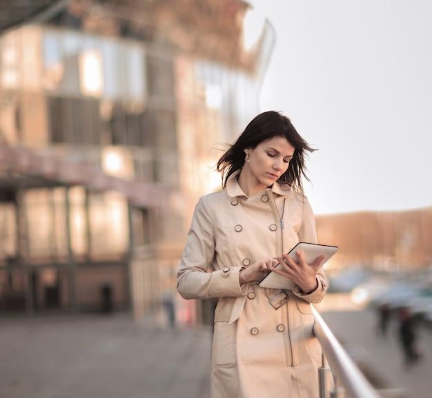 オフィスビルとデジタルタブレットを持つ現代のビジネス女性。