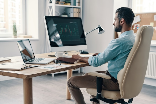 Modern business. young modern businessman analyzing data using computer while sitting in the office