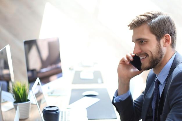 Современный бизнесмен анализирует данные с помощью компьютера и разговаривает по телефону, сидя в офисе.