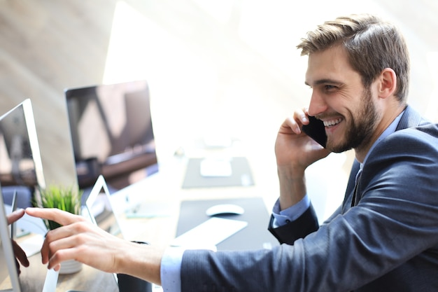 Modern businessman analyzing data using computer and talking on the phone while sitting in the office.