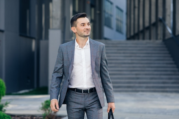 Modern businessman. confident young man in suit looking away while standing outdoors with cityscape in the background. handsome confident businessman portrait.
