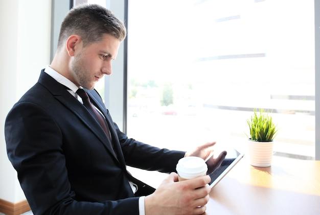 Современный бизнесмен пьет кофе в офисном кафе во время обеда и с помощью планшета