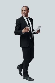 現代のビジネスマン。灰色の背景に立っている間使い捨てカップと新聞を保持する正装でハンサムな若いアフリカ人の完全な長さ
