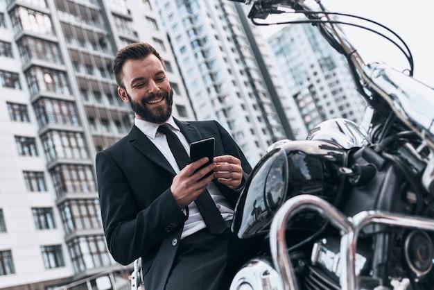 Современный бизнесмен. красивый молодой человек в полном костюме, используя свой смартфон и улыбаясь
