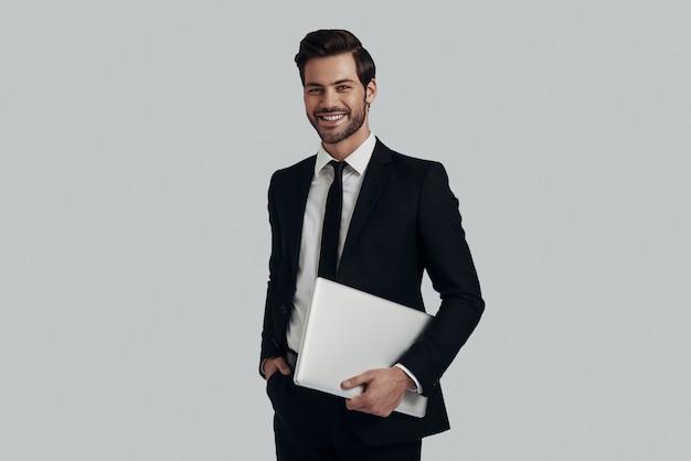 現代のビジネスマン。灰色の背景に立っている間ラップトップを運ぶ完全なスーツのハンサムな若い男