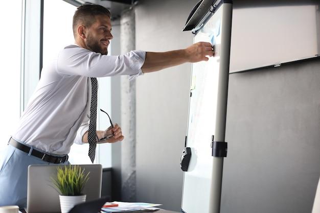Современный бизнесмен использует флипчарт в офисе. Premium Фотографии