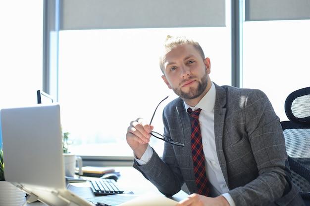 オフィスに座っている間彼の眼鏡を手に持ってカメラを見ている現代のビジネスマン。