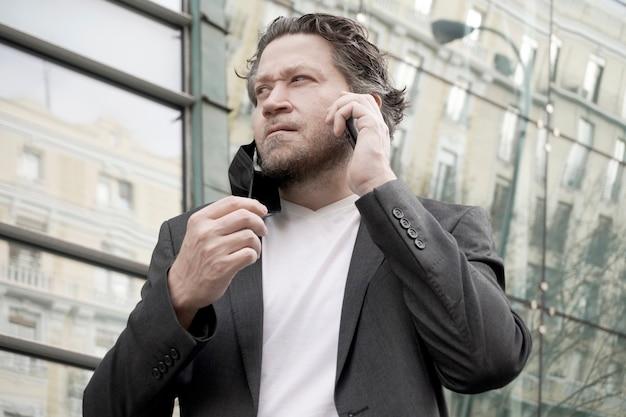 Современный бизнесмен на открытом воздухе с маской на одной стороне разговаривает по мобильному телефону на открытом воздухе