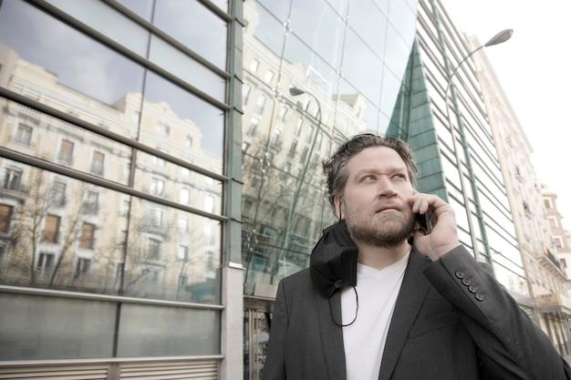 Современный бизнесмен на открытом воздухе с маской на одной стороне разговаривает по мобильному телефону