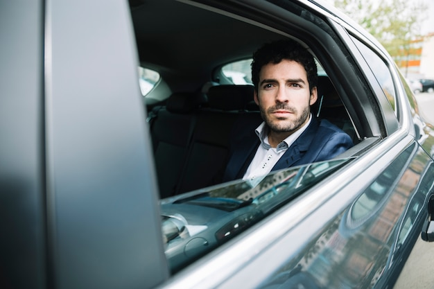 Modern businessman sitting in car