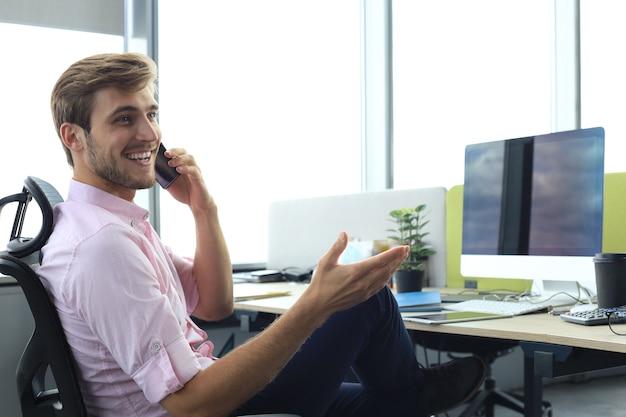 Современный бизнесмен разговаривает по телефону, сидя в офисе.