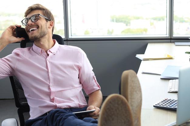 사무실에 앉아 있는 동안 전화 통화를 하는 현대 사업가.