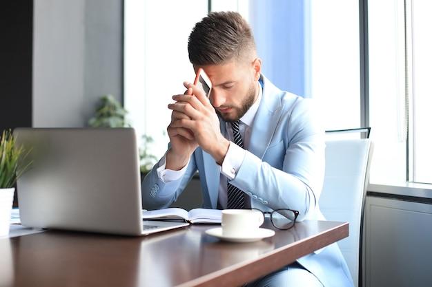 オフィスに座って何かを考えている現代のビジネスマン。