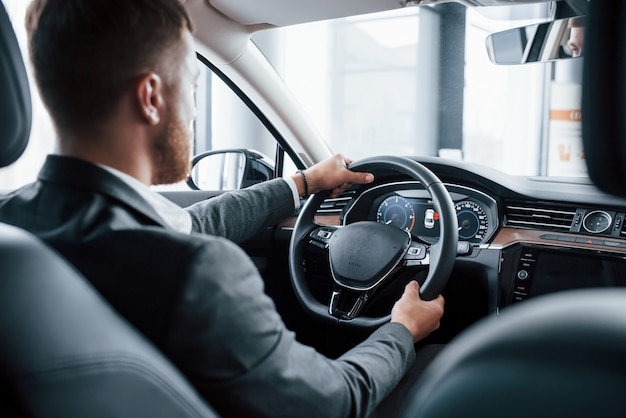 Современный бизнесмен пробует свою новую машину в автомобильном салоне