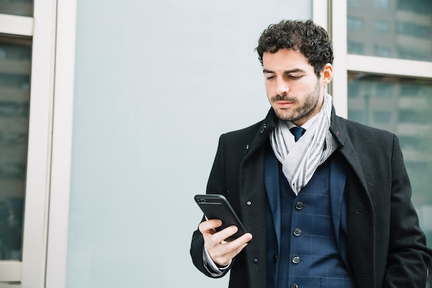 Modern businessman using device outdoors