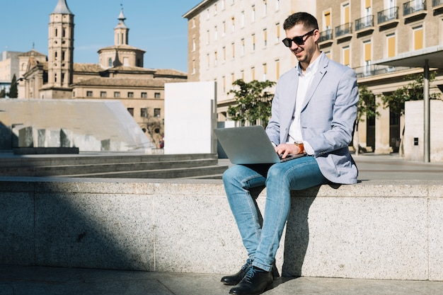 Modern businessman using laptop outdoors
