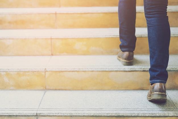 現代の都市の階段を上って歩いてクローズアップの足で働く現代のビジネスマン。急いでオフィスで働くためにラッシュアワーに。仕事の最初の朝の間。階段。ソフトフォーカス。